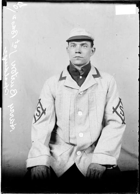 [Spalding baseball player first baseman Harry Burton, sitting in front of a light colored background in a room]
