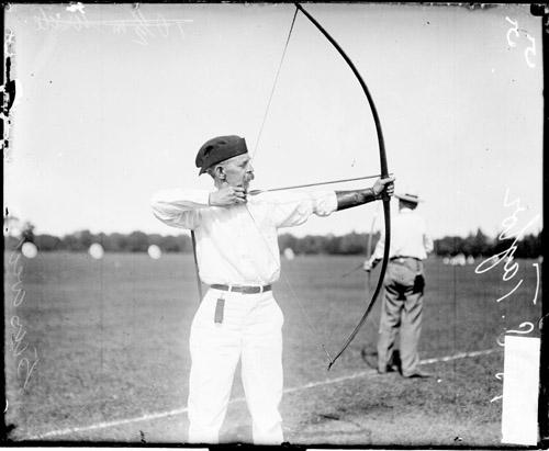 [Archer H. S. Taylor holding a bow and arrow and pulling back the bow string]