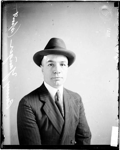 [Pugilist, Benny Yanger facing the camera wearing a suit and hat, sitting in front of a light-colored backdrop in a room]