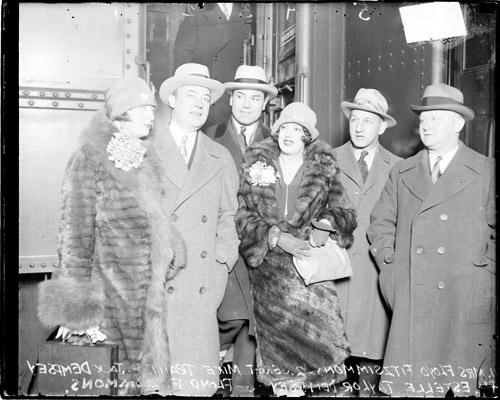 [Boxer, Jack Dempsey and his wife, Estelle Taylor Dempsey standing with Mrs. Fitzsimmons, Trant, fight promoter Fitzsimmons in a railroad station]