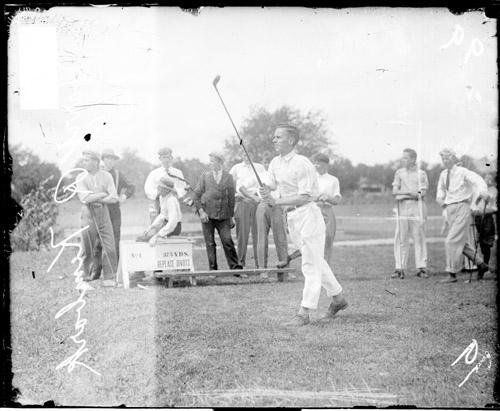 [Golfer H. R. Kimbark holding a golf club in front of him after hitting a shot]