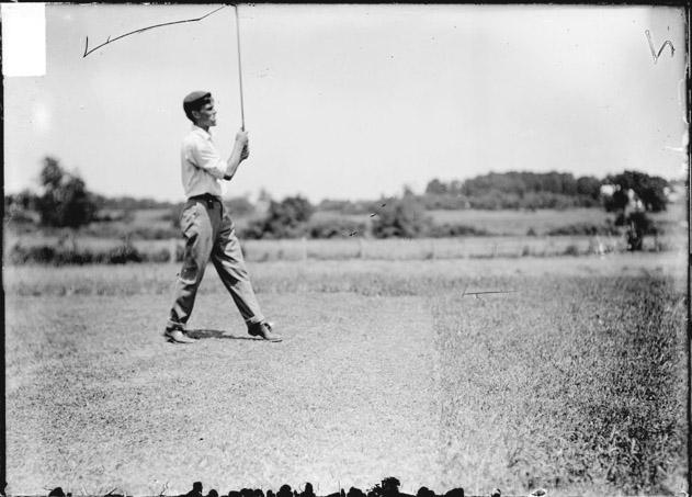 [Golfer, Js. Hollibird, standing on a golf course, holding a golf club with its head up in the air]