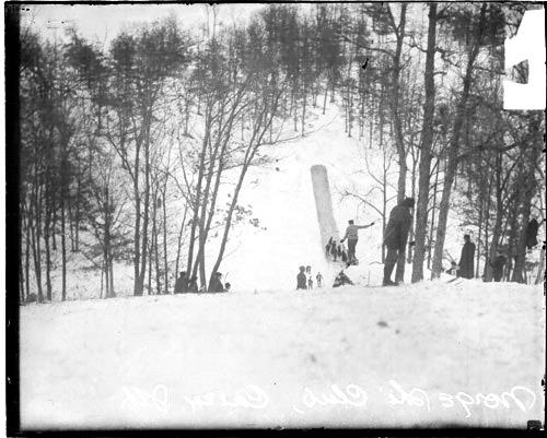 [Skier jumping off a ski jump on a snow-covered hill at the Norge Ski Club]
