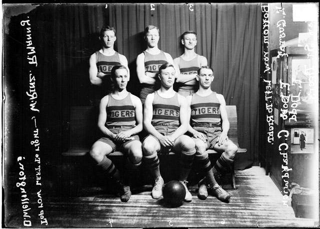 [Adams Street Tigers basketball team posing in front of a dark backdrop]