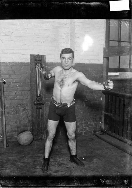 [Boxer Benny Yanger, exercising on a resistance machine in a gymnasium]