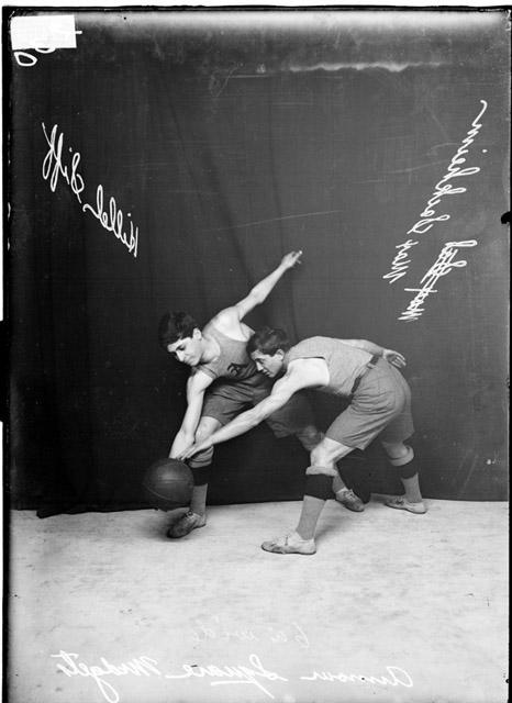 [Armour Square Midgets basketball players, Siff Hillel and Max Sackheim, standing in a basketball stance in front of a dark backdrop]