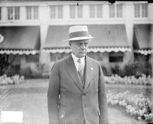 [Horse racing, C. Ray, C. Ray standing in front of a building at the Washington Park Race Track]