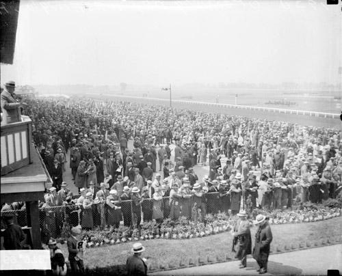 [Crowds standing in front of grandstands and lining a railing on Opening Day at Washington Park Race Track]