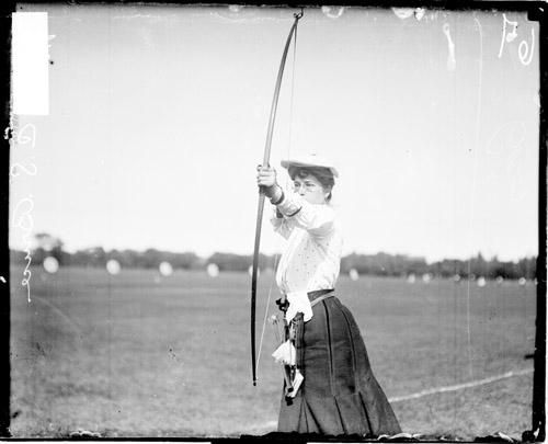 [Archer Miss C. S. Bruce holding a bow and arrow and pulling back the bow string]