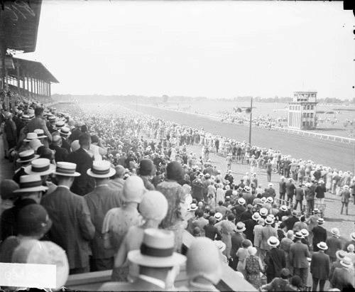 [Crowds standing in and in front of grandstands watching a horse race at Washington Park Race Track]