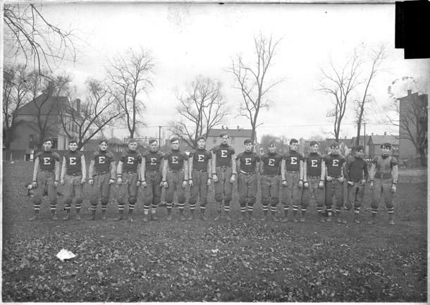 [Football team, Englewood High School, dark exposure, lined up on field]