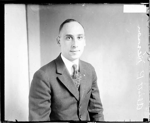[Abbott P. Herman wearing a suit, sitting in front of a light-colored backdrop in a room]