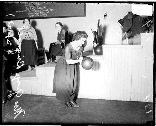 [Bowler, Mrs. George Brignall holding a bowling ball and leaning forward, standing in front of a tiered structure in a room]