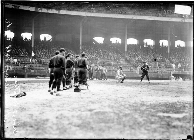 [Baseball, City Series, Cubs player at bat while teammates watch from foul zone at Comiskey Park]