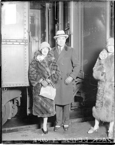 [Boxer, Jack Dempsey and his wife, Estelle Taylor Dempsey, standing in front of a passenger train car]