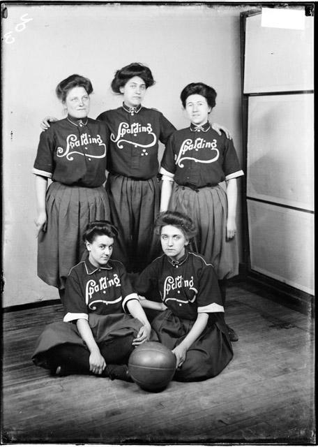 [Spalding Women's Basketball players posing by a backdrop, women in front are sitting on floor]