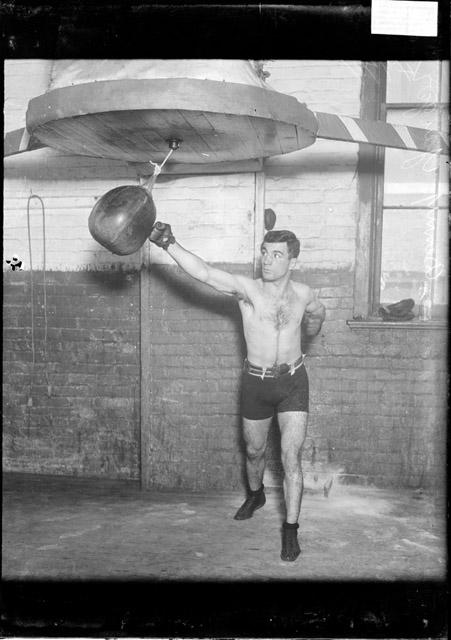 [Boxer Benny Yanger, punching a speed bag with his right hand in a gymnasium]