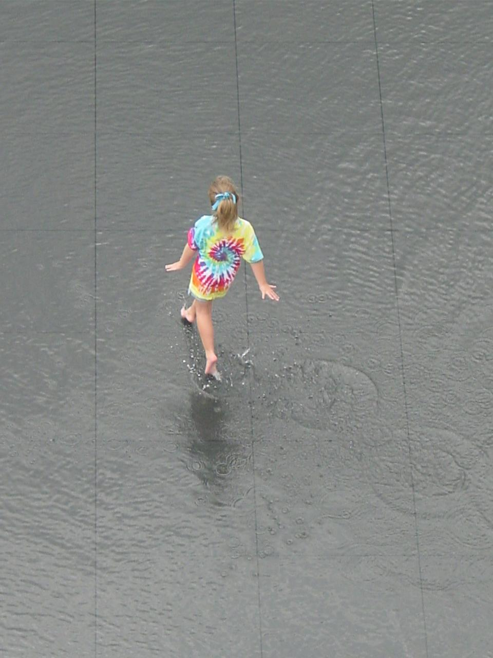 Crown Fountain, a child plays in the reflecting pool, opening day, July 16, 2004
