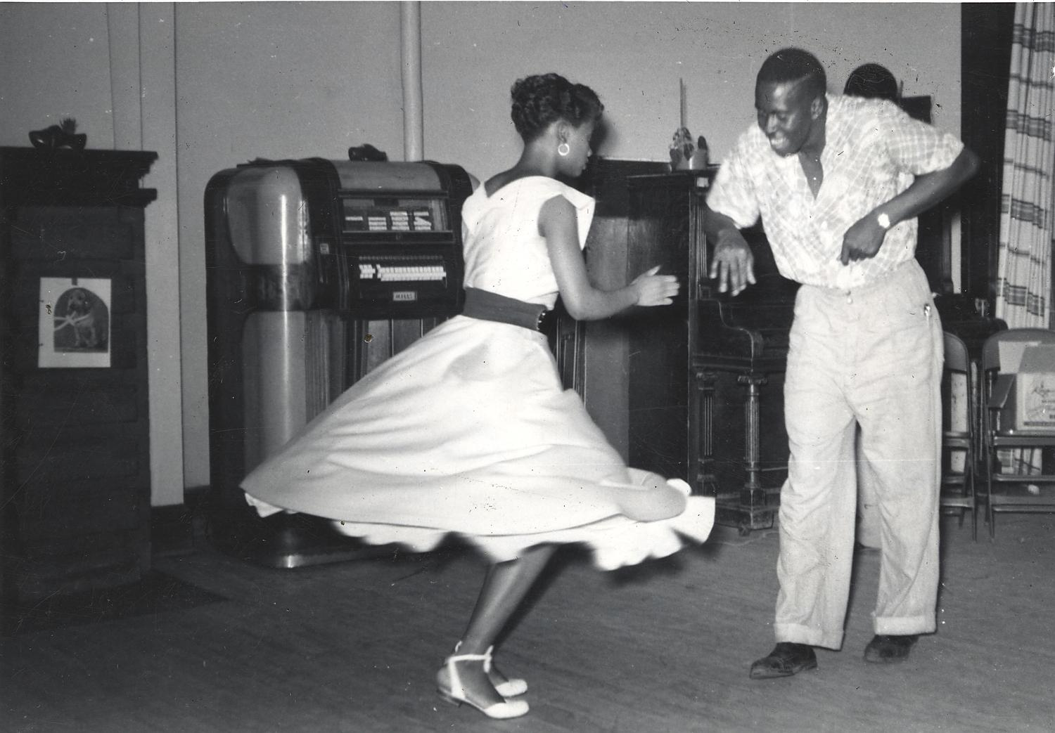 One African American couple dancing in front of jukebox