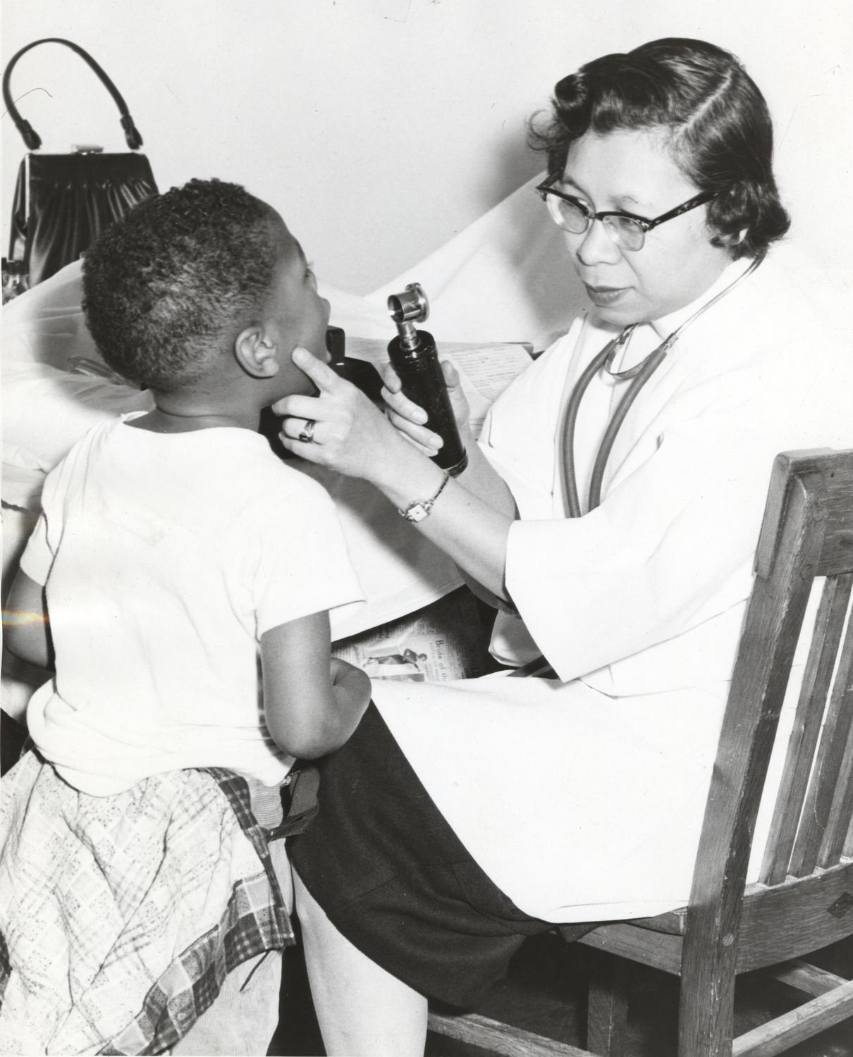 Doctor looking into the mouth of a young African American boy