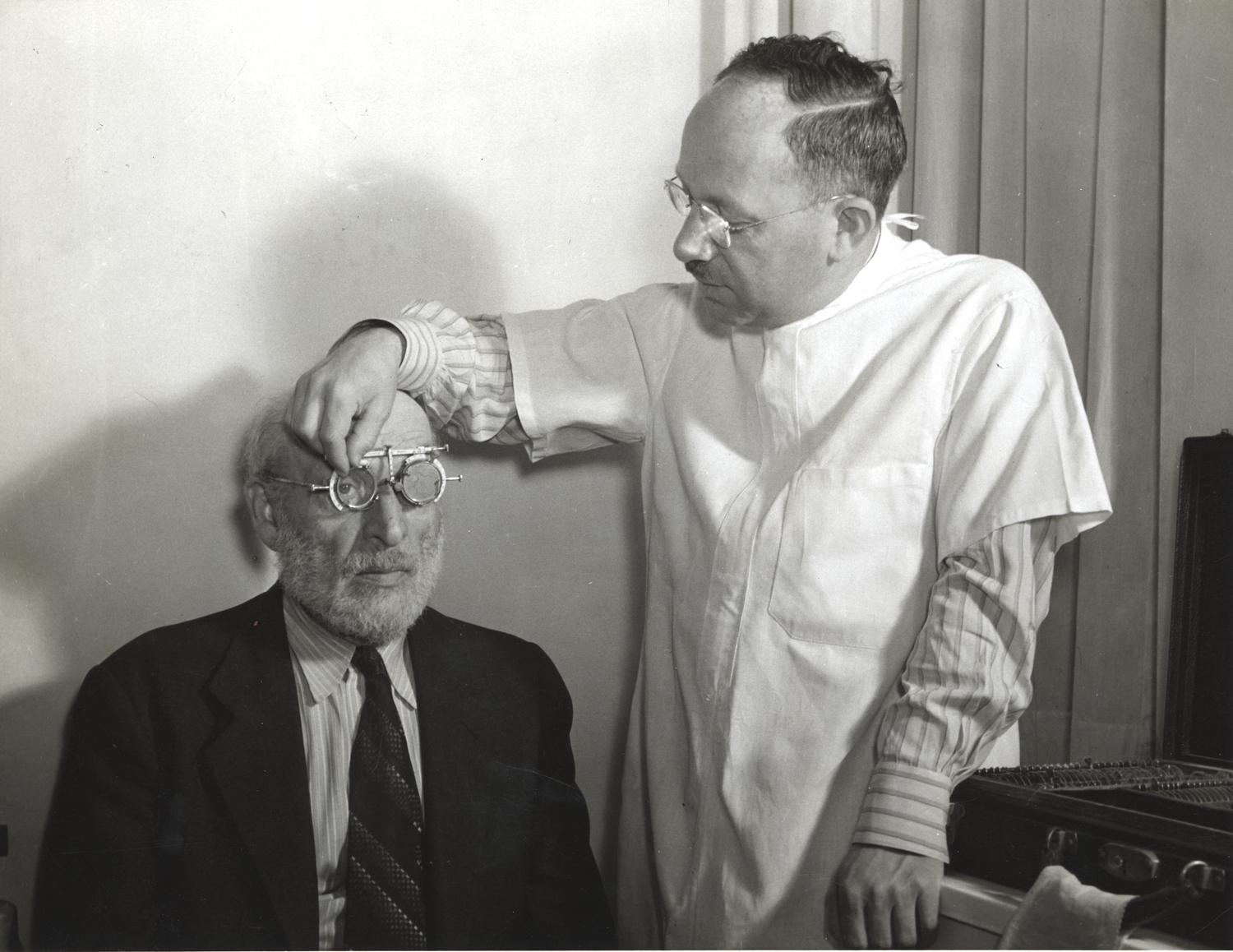 Doctor giving eye test to an older man