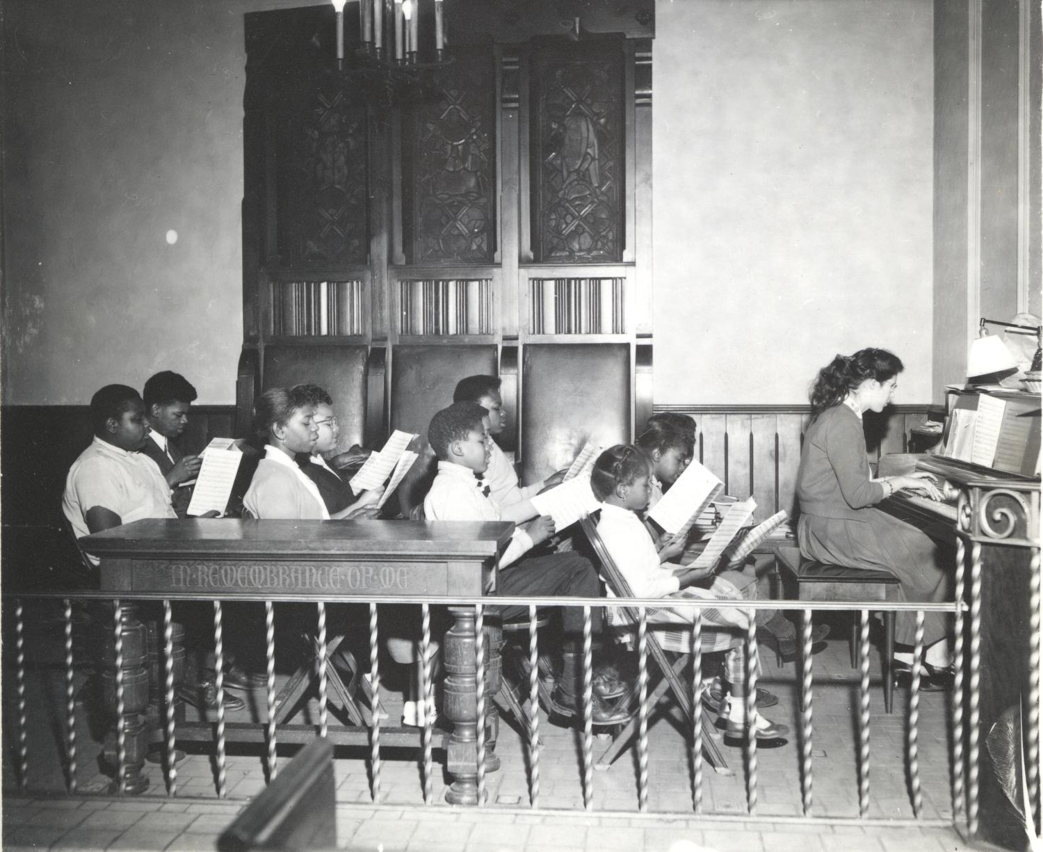 Children singing from sheet music with a woman playing piano
