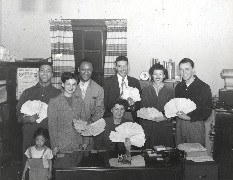 Adults holding checks in a fan-shape