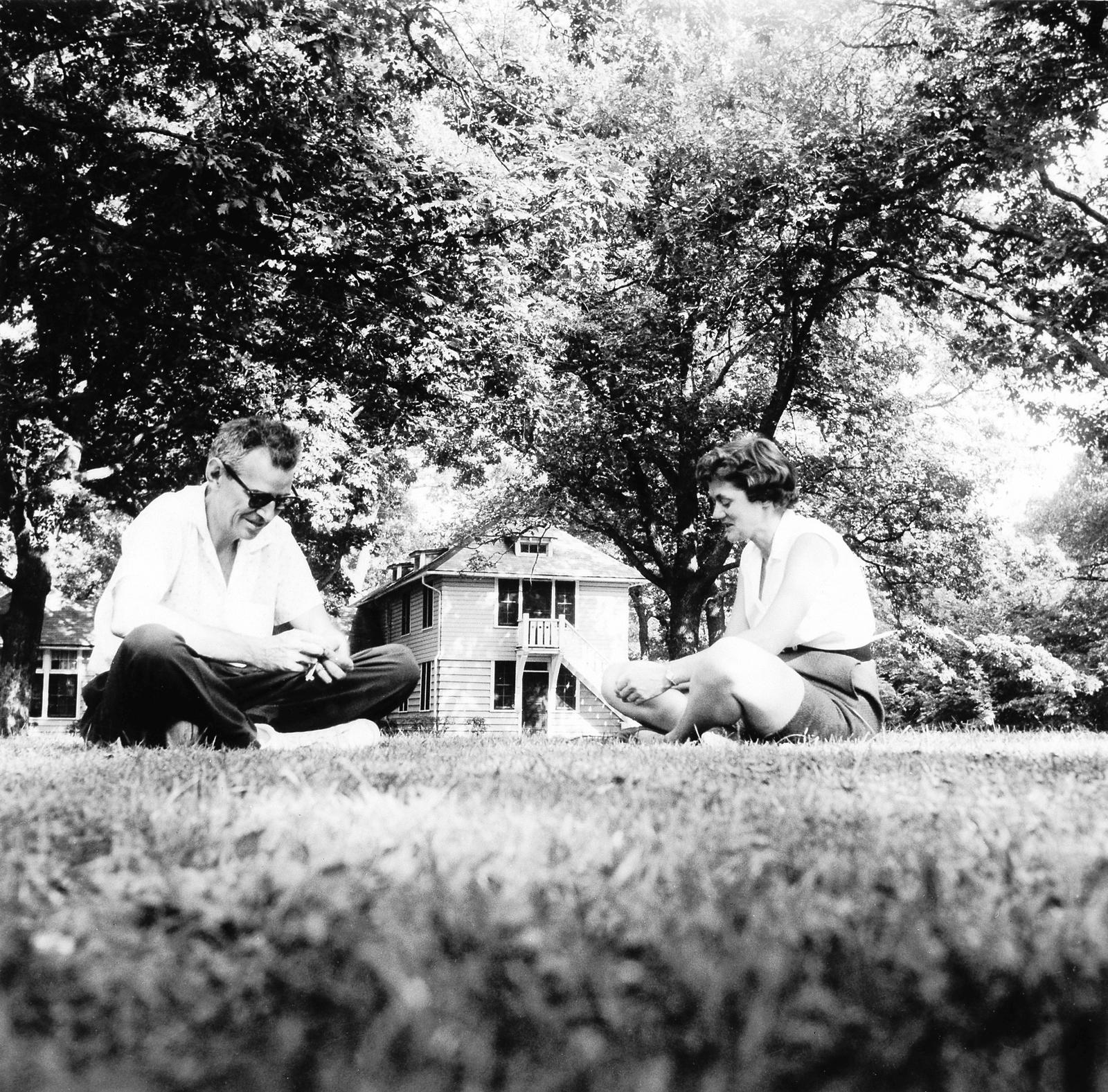 Adults, looking down, sitting on lawn in front of Smith Cottage.