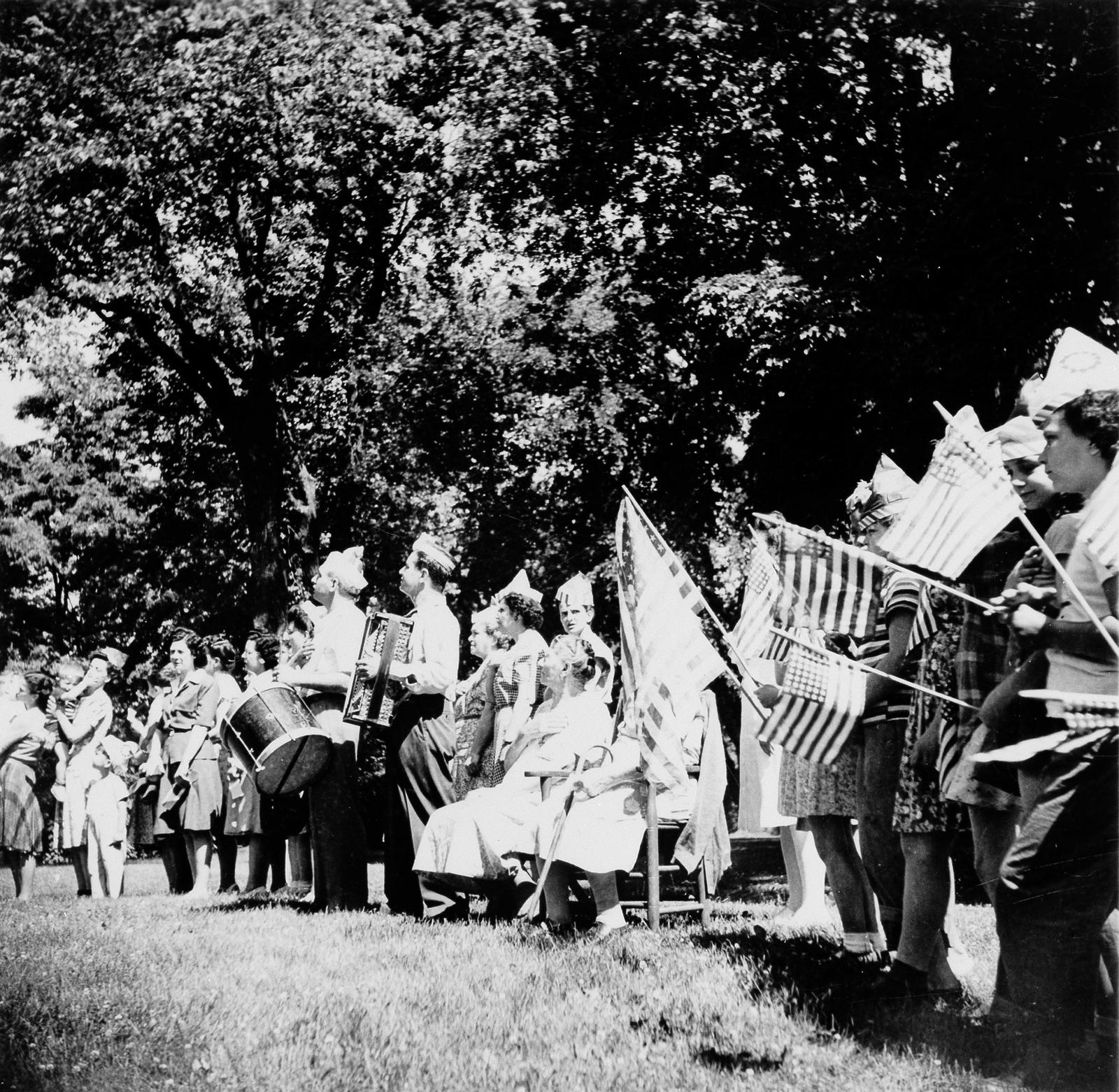 Children with drum, accordian, and flags