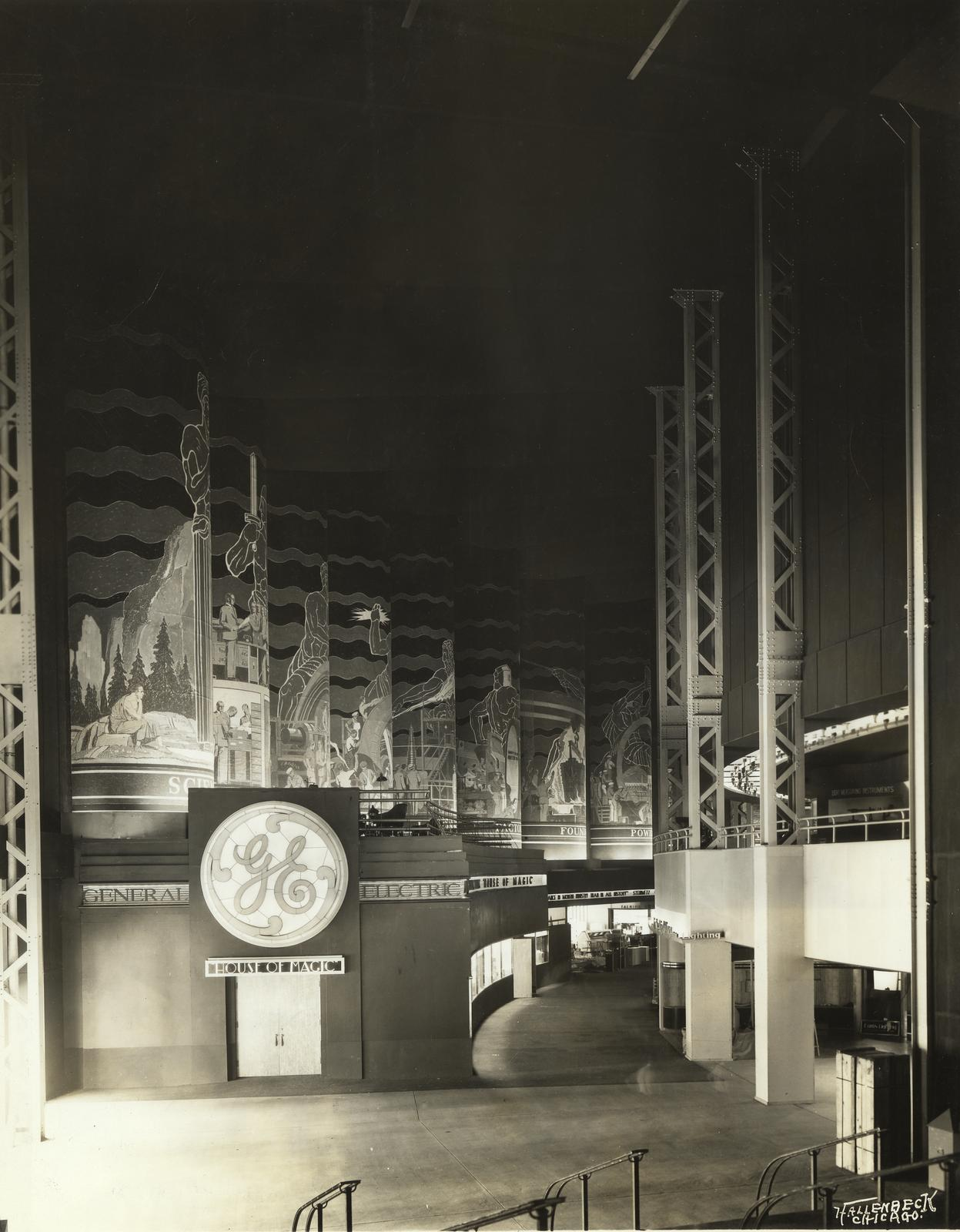 """Above the 'House of Magic,' in which General Electric presents demonstrations of spectacular research laboratory developments, and extending along the entire length of a balcony over the exhibit space is a series of thirteen huge pillars covered with mur"